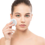 Young woman cares for face skin. Cleaning perfect fresh skin using cotton pad. Isolated. stock images