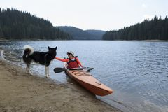 Young woman caress Alaskan Malamute sitting in her kayak. Selective focus Royalty Free Stock Image