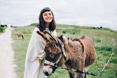 Young woman caresses a happy donkey. Happy and optimistic woman unites with nature by caressing funny cute donkey, hugs him and laughs into camera royalty free stock photos