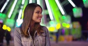 Young woman at carnival stands looking up in awe. And smiles in front of ferris wheel stock footage