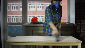 Young woman carpenter removes wood dust from countertop using vacuum cleaner. The process of building a wooden table, a woman carpenter removes the wood dust stock footage