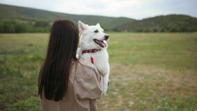 Young woman carries on hands and kissing a white swiss shepherd dog on the outdoor lawn.