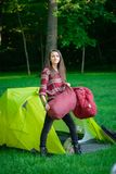 A young woman sleeping bags in a tent while camping. A young woman carries sleeping bags to put in the tent while camping outdoors Stock Image