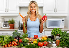 Young woman with carrot in the kitchen. Stock Photo