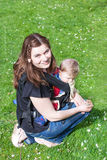 Young woman carrying baby in rucksack in park Stock Photo