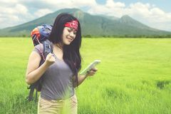 Young woman walking in the field flower. Young woman carrying a backpack while walking in the field flower to trek a mountain Royalty Free Stock Image