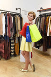 Young woman carrying bags shopping at fashion boutique choosing clothes smiling happy Stock Photos