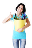 Woman carrying a bin with recyclable glass bottles. Stock Image