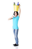 Woman carrying a bin with recyclable glass bottles. Stock Photo