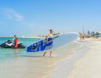 Young woman carrying board at Kate beach in Dubai. Family making vacations and enjoying summer. Royalty Free Stock Photography