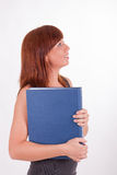 A young woman is carrying a book Stock Photography