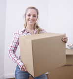 Young woman carrying box Stock Photos