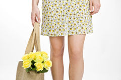 A Young Woman Carrying A Bunch Of Yellow Roses In A Shopping Bag Royalty Free Stock Photography