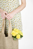 A Young Woman Carrying A Bunch Of Yellow Roses In A Shopping Bag Stock Image