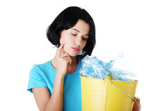 Woman carrying a container with empty recyclable plastic. Royalty Free Stock Images