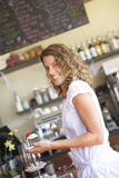 Young woman carrying dessert in cafe, smiling, side view, portrait (tilt) Stock Photos