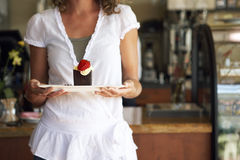 Young woman carrying dessert on serving dish in cafe, mid-section, front view Stock Images