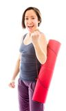 Young woman carrying exercise mat celebrating success Royalty Free Stock Images