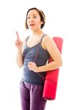 Young woman carrying exercise mat pointing her finger up Royalty Free Stock Image