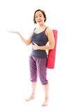 Young woman carrying exercise mat presenting Royalty Free Stock Photo