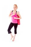 Young woman carrying exercise mat smiling and pointing Royalty Free Stock Images