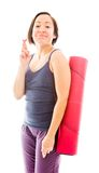 Young woman carrying exercise mat wishing with crossing fingers Stock Photos