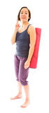 Young woman carrying exercise mat wishing with crossing fingers Royalty Free Stock Photo