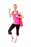 Young woman carrying exercising mat and celebrating success Royalty Free Stock Photography