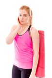 Young woman carrying exercising mat looking sad Royalty Free Stock Images