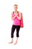 Young woman carrying exercising mat shivering in cold Stock Photo
