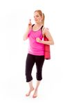 Young woman carrying exercising mat wishing with crossing finger Stock Images