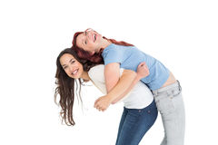 Young woman carrying female friend on back Stock Photo