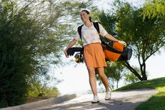 Young Woman Carrying Golf Bag Royalty Free Stock Image