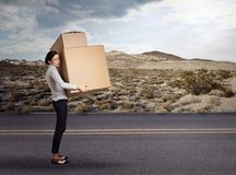 Young woman carrying heavy large box package. Young funny looking tired woman carrying heavy large box package walking down the countryside road Stock Images