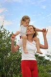 Young woman carrying her daughter over the shoulde Stock Photos
