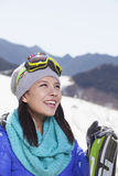 Young Woman Carrying Her Skis Stock Photo