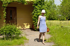 Young woman carrying jug by the summer house Stock Photos