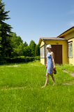 Young woman carrying jug by the summer house Stock Photo