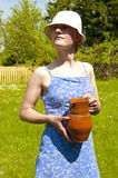 Young woman carrying the jug with the water. Summer work theme shot Stock Image