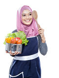 Young woman carrying a pan full of vegetables and wooden spatula Stock Images