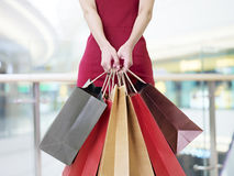 Young woman carrying paper shopping bags in modern mall. Young woman female shopper standing with colorful paper bags in hands in shopping mall or department Royalty Free Stock Images