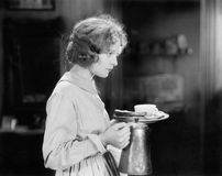 Young woman carrying a pot of coffee and a plate with bread. (All persons depicted are no longer living and no estate exists. Supplier grants that there will be Royalty Free Stock Image