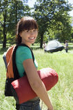 Young woman carrying rucksack and sleeping bag to camp in woodland clearing, smiling, portrait, friends assembling tent Stock Photography