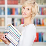 Young Woman Carrying Stacked Books In Library Stock Image