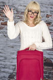 Young Woman Carrying a Suitcase Waving Royalty Free Stock Photography