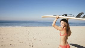Young woman carrying a surfboard at the beach. stock video