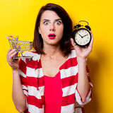 Young woman with cart and alarm clock Stock Photography