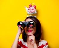 Young woman with cart, binoculars and alarm clock Stock Photography