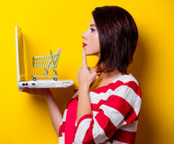 Young woman with cart and laptop Stock Photo