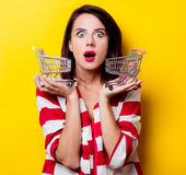 Young woman with carts. Portrait of the beautiful young woman with carts for shopping on the yellow background Royalty Free Stock Photo